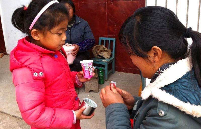 家长幼儿园门外给孩子喂饭