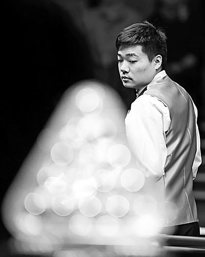 月13日,中国选手丁俊晖在经过大师赛冠军奖杯时