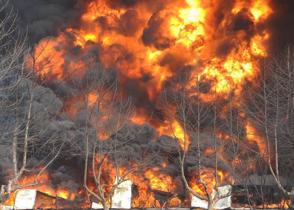 2013年3月7日,山东青岛保税港区一橡胶仓库燃起的大火,消防人员正在