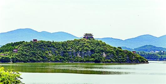 """图为:已废弃的桃花岛。 昔日桃花笑春风 而今人面不知处 洈水库区几百座湖心岛中,有一处岛屿,名曰桃花岛,以其神秘的传闻和独特的景观,吸引了我们的目光。 桃花岛四面环水,面积14万平方米。上世纪90年代,湖南开发商在洈水湖区投资近千万,征地造景,修建了这个度假休闲胜地。岛上桃树遍种,仿古建筑气息浓厚:岛屿顶端建造了微缩版""""万里长城"""",可登上观岛内全景;巍峨的""""楚乐宫""""屹立于古城台楼,可欣赏歌舞表演;度假村红墙碧瓦,亭台楼阁,隐在桃林之中。一时间,桃花岛名声大"""